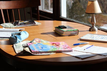 My kitchen table, cluttered as always with the artifacts of busy minds.